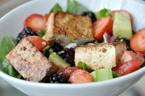 Berry Salad with orange sesame Tofu in a white bowl