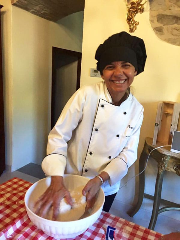 A female chef with a black chef's hat making pasta