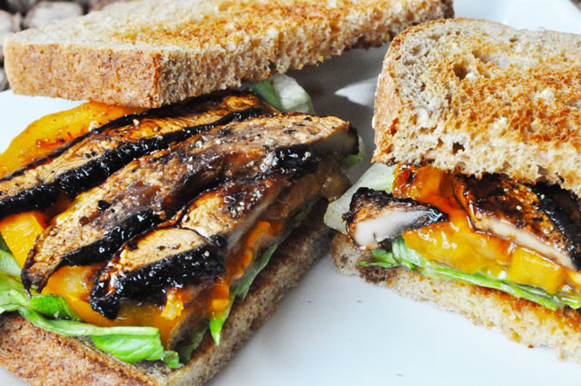 Portobello Mushroom Bacon BLT sandwich with the toast half on, on one half of the sandwich on a white plate