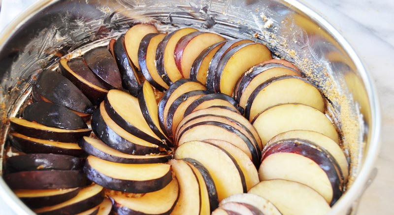 sliced plums arranged in a spiral in a buttered spring form pan