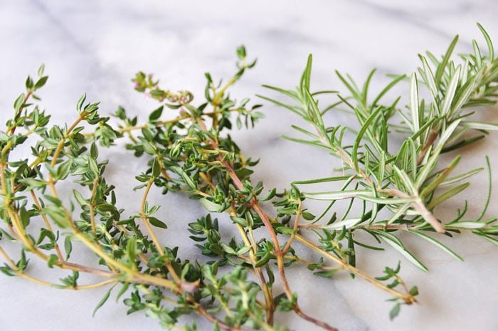 Sprigs of fresh thyme and rosemary on a marble surface