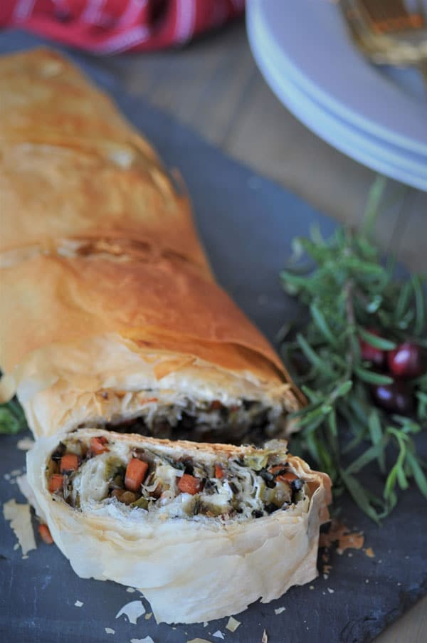 Vegan Vegetable Wellington, sliced on a gray slate board with fresh herbs and cranberries for garnish.