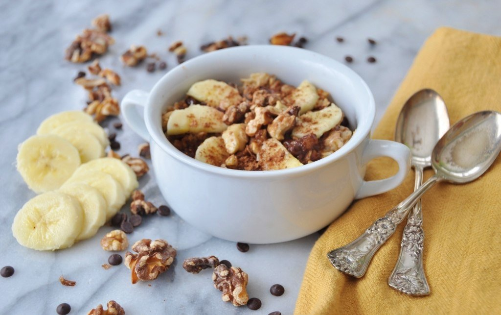 Vegan Chocolate Banana Bread Oatmeal in a white bowl with sliced bananas, walnuts, and chocolate chips sprinkled next to it and two silver spoons and a gold napkin
