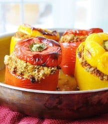 Vegan Lentil Quinoa and Vegetable Stuffed Peppers in a copper pan with the tops of the peppers on