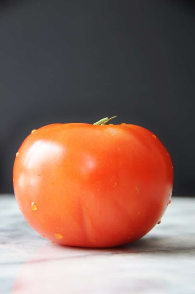 A red tomato with water droplets on the skin.