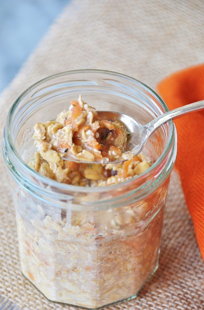 Vegan Carrot Cake Overnight Oats in a glass mason jar with a silver spoon in the jar and a burlap cloth and orange napkin under and next to the jar