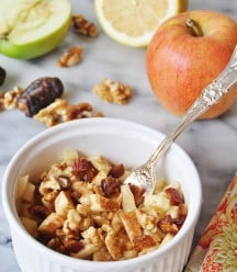 Raw Apple Pie in a white bowl with a silver fork in the bowl, and a red apple and half of a green apple and a lemon, and walnuts in the background