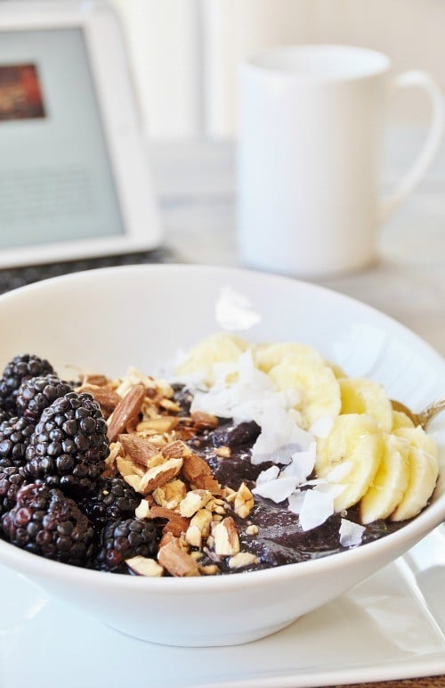 Vegan Berry Banana Smoothie Bowl in a white bowl with a white coffee mug and a laptop in the background