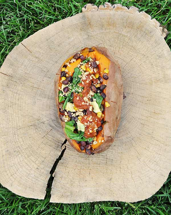 Mexican-Stuffed-Sweet-Potato on a piece of wood with a crack in it in the grass