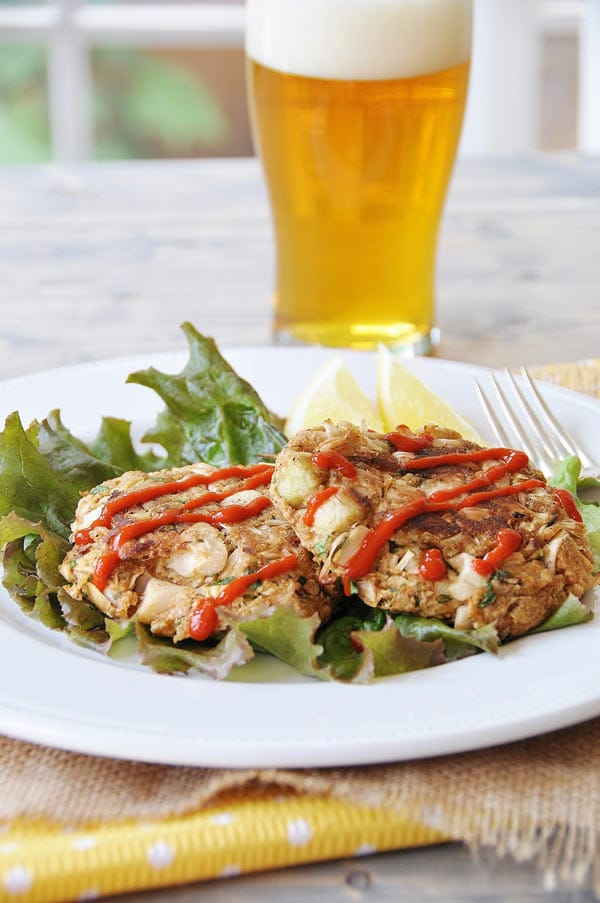 Crab cakes on a white plate and a bed of lettuce with sriracha and a beer in the background.