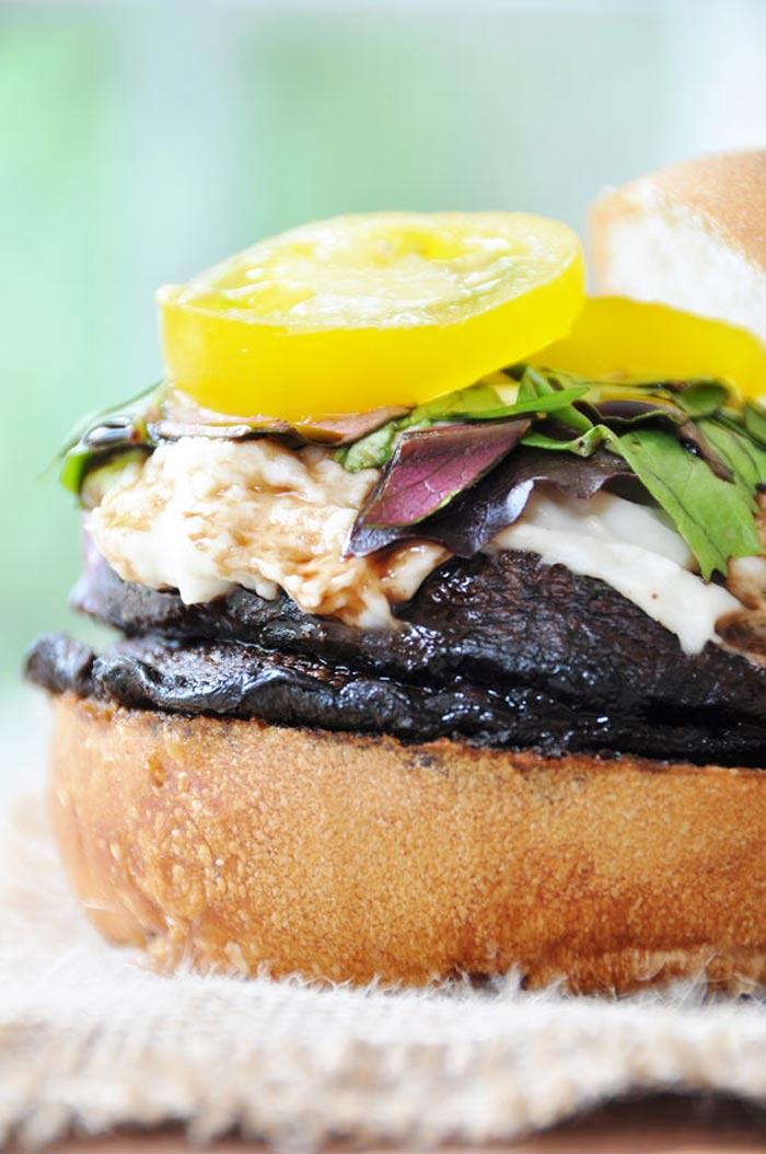 A mushroom burger with mozzarella, lettuce, and a yellow tomato.