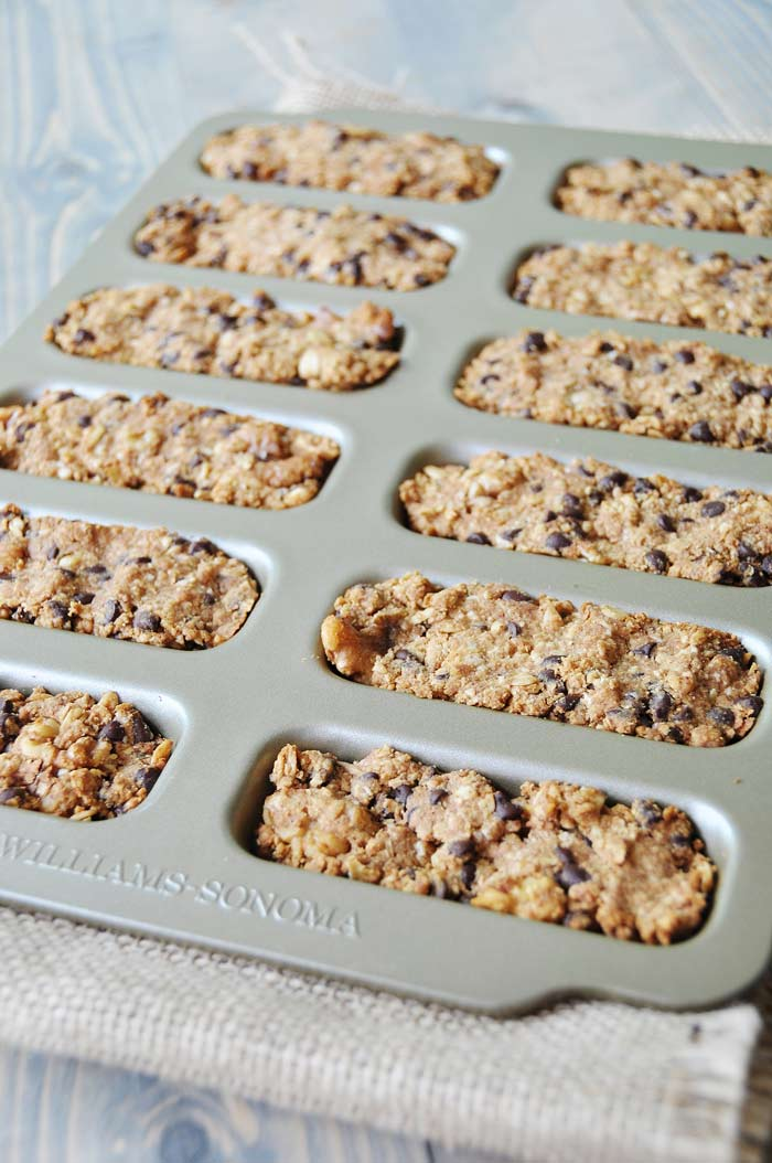 Vegan Peanut Butter Oatmeal Chocolate Chip Granola Bars in a bar baking pan on burlap and a wood board
