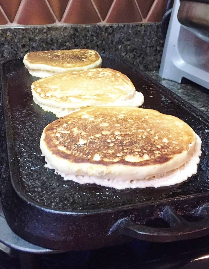 Golden brown fluffy vegan pancakes cooking on the griddle.