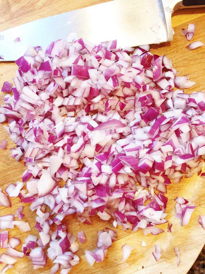 Finely-Chopped-red onions on a wooden cutting board with a chef's knife