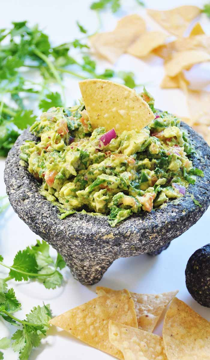 Spinach Guacamole Made in a Molcajete . The molcajete stone bowl makes this spinach guacamole recipe so flavorful and fun to make. The spinach adds protein, iron, and vitamins, and it boosts the volume, and only you will know it's in there. www.veganosity.com