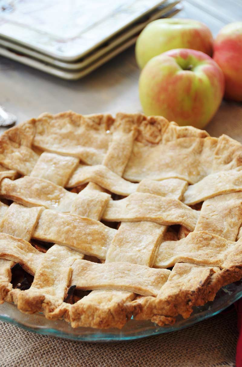 Homemade Apple Cinnamon Pie with a lattice top crust in a glass pan with three red apples and three square plates behind it.