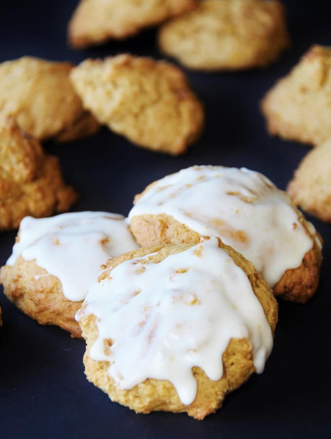 3 vegan pumpkin spice cookies frosted with a sugar glaze.