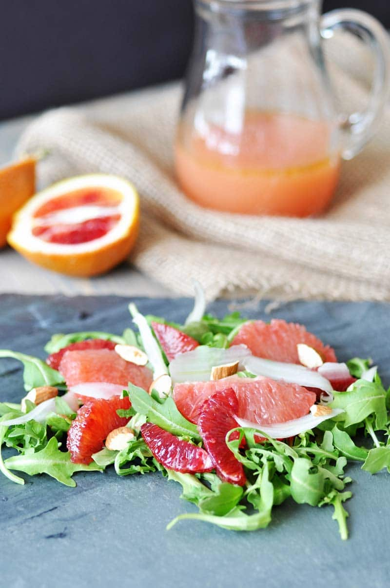 Winter Citrus & Arugula Salad with Cranberry Orange Dressing. This fresh and bright salad recipe will take away your winter blues. Red grapefruit, blood orange, fennel, and raw almonds. www.veganosity.com