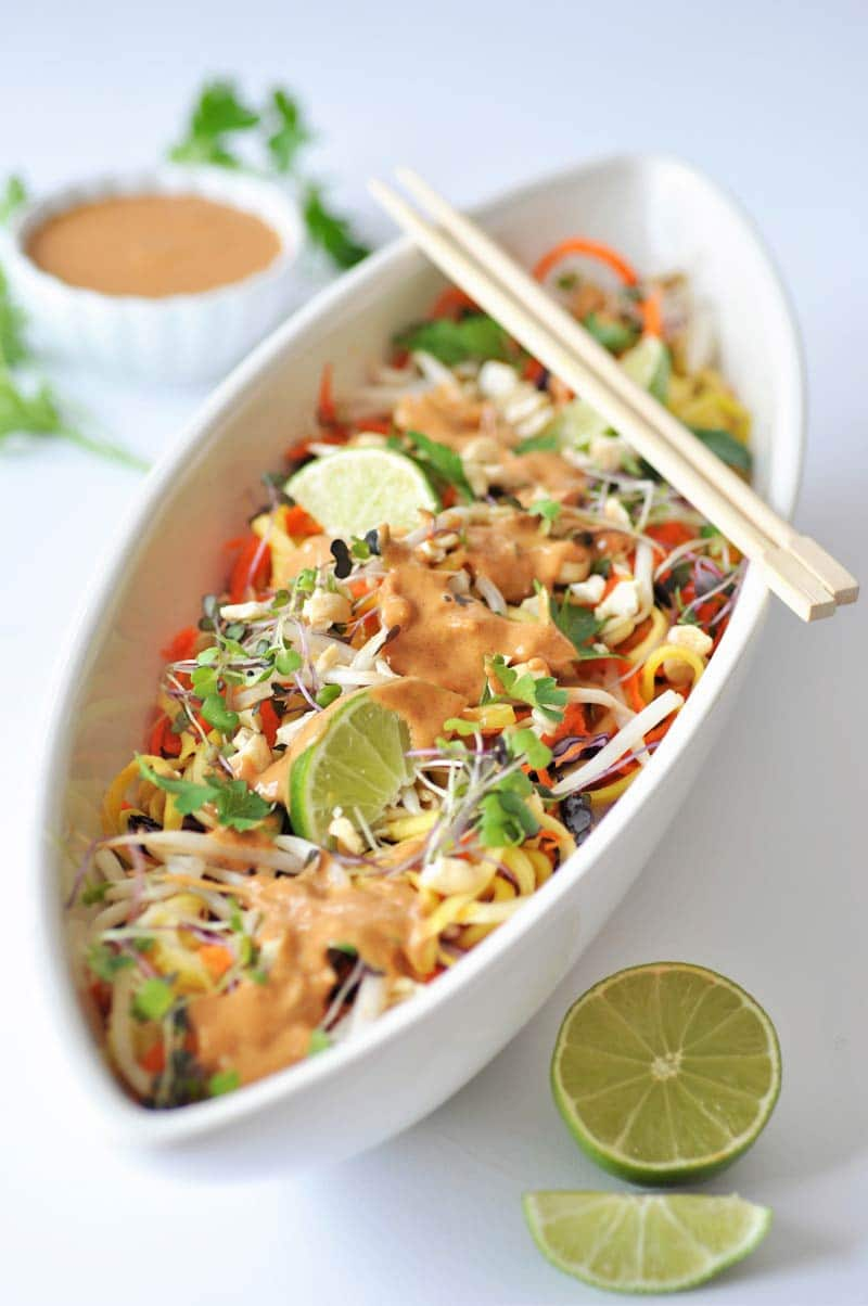 Super--Sprouts Pad-Thai-with-Spicy-Peanut-Sauce in a long white bowl with a pair of chopsticks on top and a lime and a the peanut sauce in a small white bowl in the background.