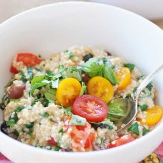 A white bowl with oats, tomatoes, and spinach with a spoon sticking out of the bowl.