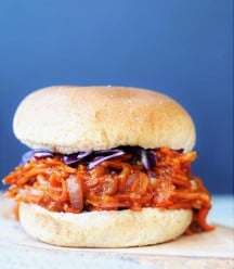 Pulled BBQ-Carrots with Homemade BBQ Sauce Sandwich on a wood board with shredded red cabbage