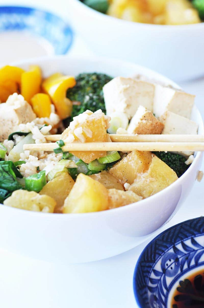 A white bowl with rice, pineapple, and broccoli and chopsticks picking up a piece of pineapple