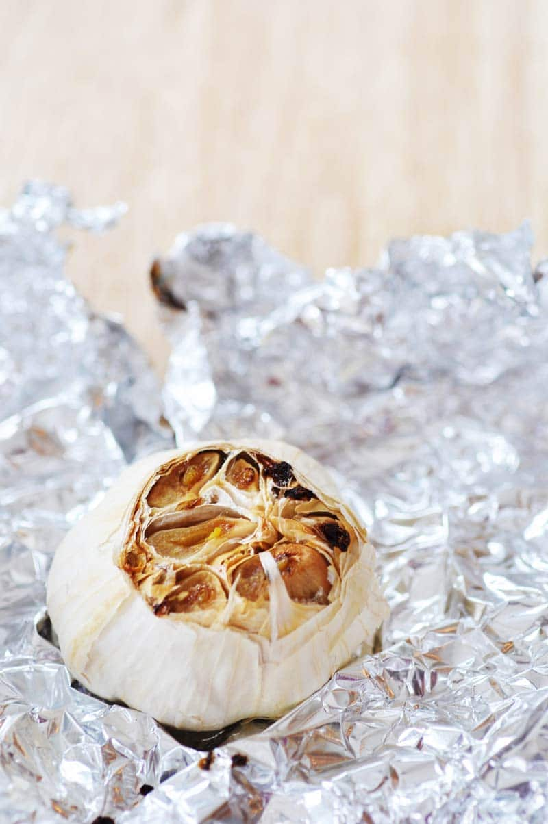 A head of roasted garlic on a piece of foil.