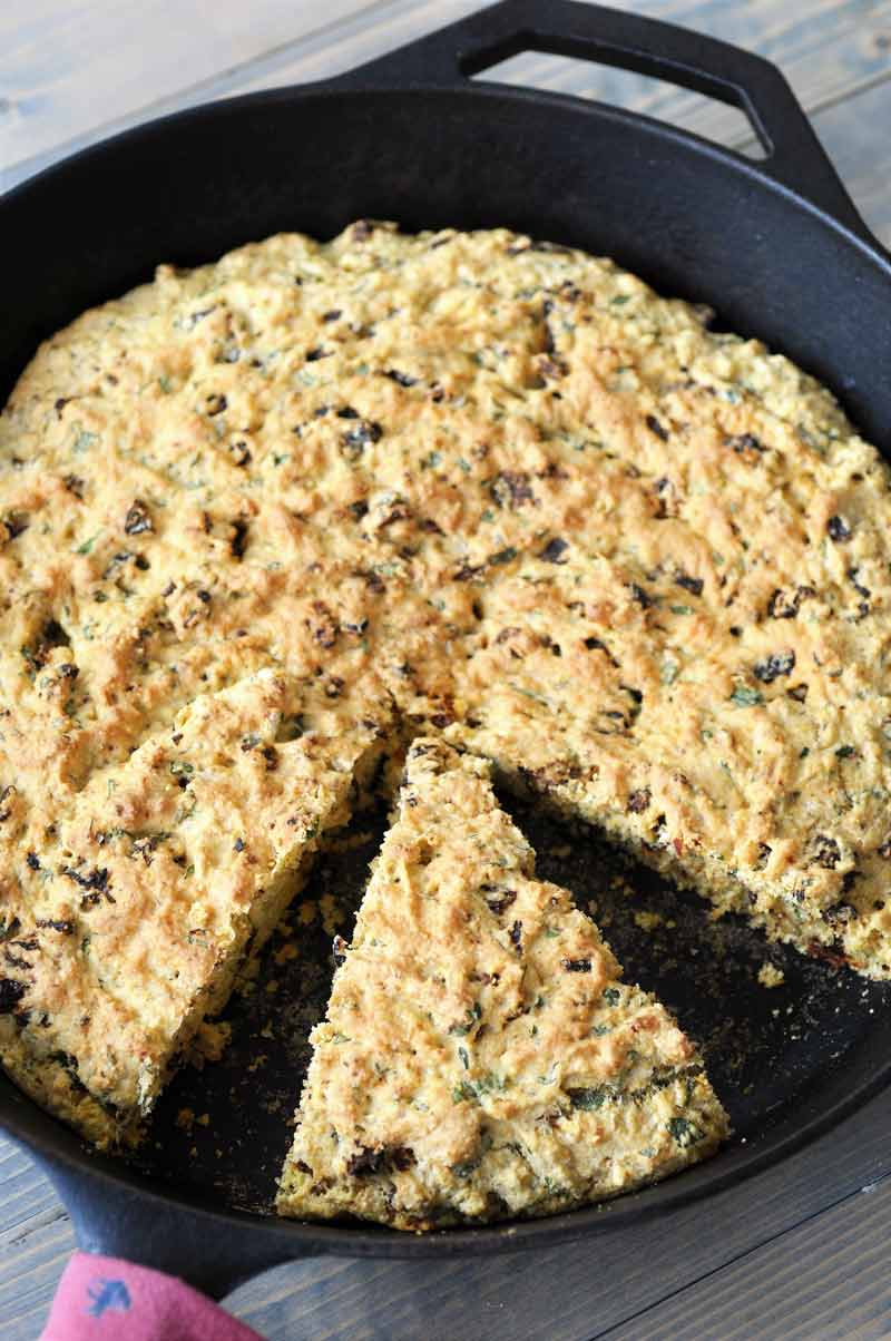 Savory Vegan Italian Cornbread! This flavorful cornbread recipe is filled with sun dried tomatoes and fresh rosemary and basil. This is not your grandma's cornbread. www.veganosity.com