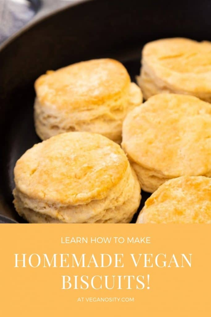 A Pinterest pin for vegan buttermilk biscuits with a picture of the biscuits in an iron skillet.