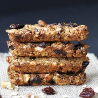 Granola bars stacked on a burlap cloth with nuts and dried fruit around them.