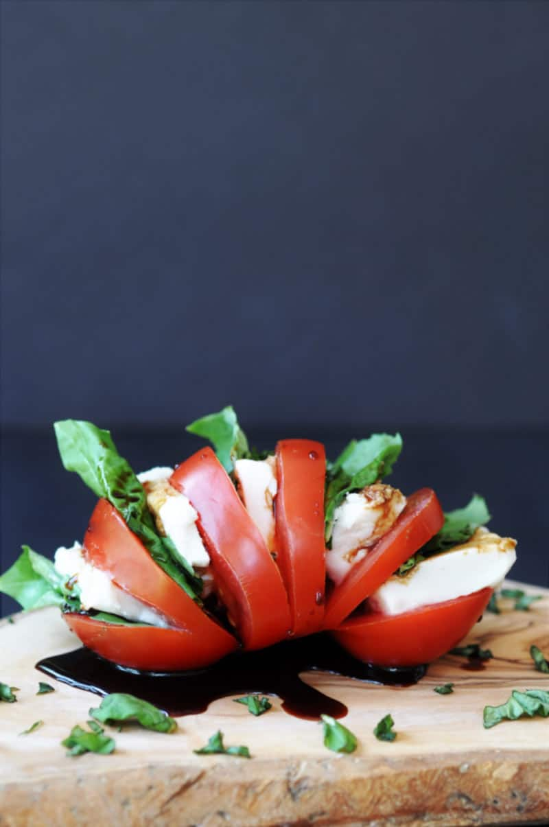 Single Serving Vegan Caprese Salad on a wood board with chopped basil sprinkled around on it and a black background