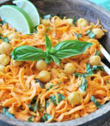 A wooden bowl with spiralized sweet potatoes, chickpeas, and basil with a pair of chopsticks in the bowl.