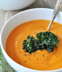 Carrot soup topped with kale chips in a white bowl with a silver spoon in the bowl. Sprigs of rosemary and another bowl of soup are next to the bowl of soup.