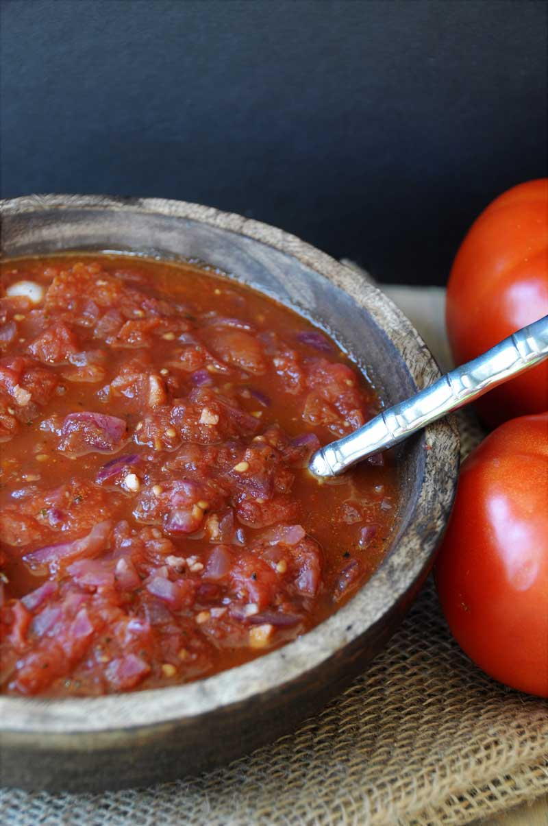 A wooden bowl filled with red tomato spaghetti sauce with a silver spoon in the bowl and tomatoes to the right of the bowl.