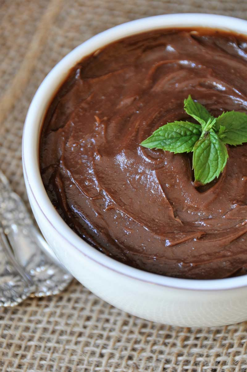 Silky smooth chocolate pudding in a white bowl with a sprig of mint on top on a burlap cloth with two silver spoons next to it.