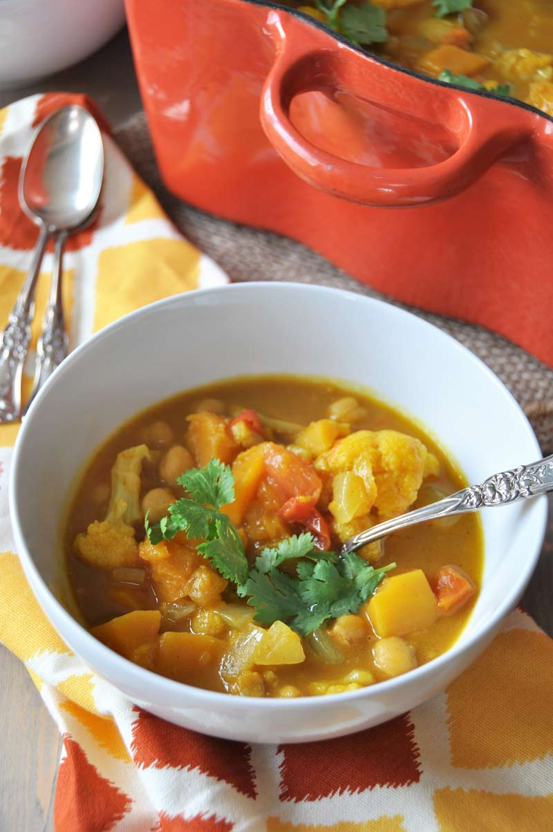Curried pumpkin and butternut squash stew in a white bowl with a sprig of cilantro on top and a silver spoon in the bowl, sitting next to an orange Dutch oven filled with stew.