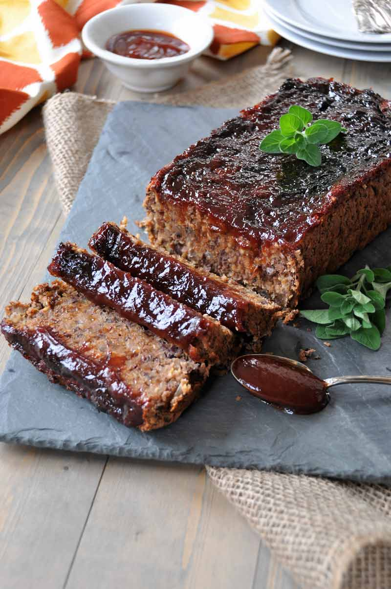 Sliced Vegan meatloaf on a slate platter with a spoon of sauce next to it and fresh sprigs of oregano and a dish of BBQ sauce and white plates in the background