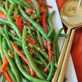 Spicy flash fried green beans with red peppers and pepper flakes on a white platter with gold utensils resting on the edge of the platter on an orange cloth