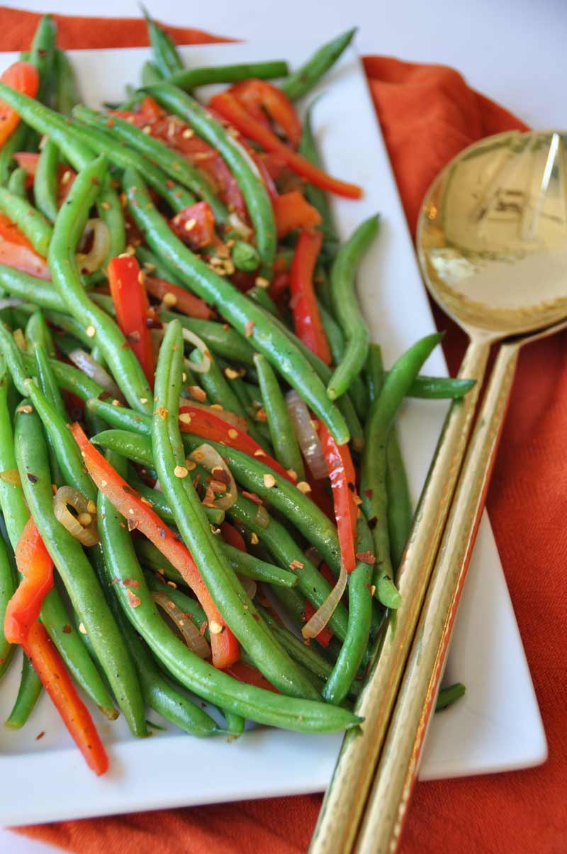 Spicy flash fried green beans, red peppers, and shallots! The perfect side dish recipe for the holidays! www.veganosity.com