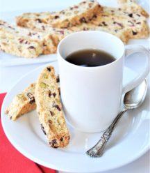 A white mug with coffee on a white saucer with a silver spoon and 2 biscotti cookies on the saucer, and a platter of the biscotti in the background.