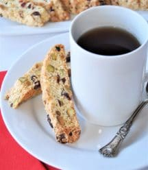 Cranberry biscotti on a white plate next to a white ceramic cup of coffee with a silver spoon resting on the edge of the plate and a red napkin next to the plate and a white plate of cookies in the background