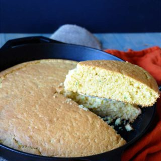 vegan cornbread in an iron skillet with a piece being removed from the pan