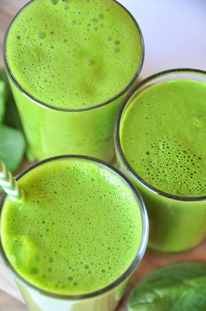 3 glasses of 5 ingredient homemade green juice with spinach, apple, lemon, and turmeric. A healthy and tasty way to drink your veggies.