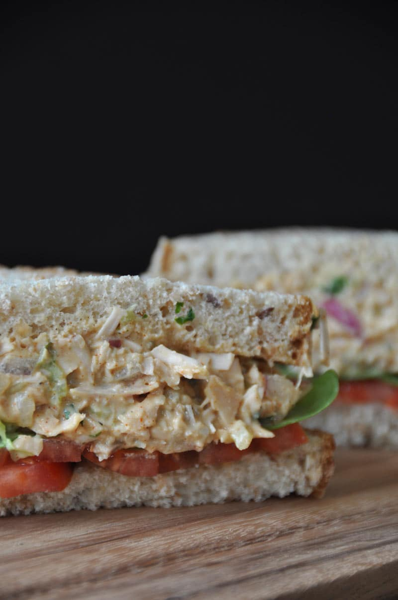 A jackfruit tuna-less salad sandwich cut in half with whole grain bread, lettuce and tomato on a wood board