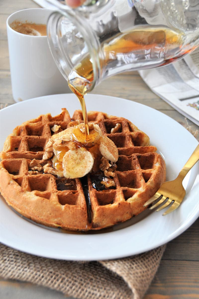 A banana bread waffle on a white plate with banana slices and walnuts on top. There is a gold fork on the rim of the plate and a glass pitcher is being held above the waffle and syrup is pouring over it. A white coffee mug and a newspaper are in the background