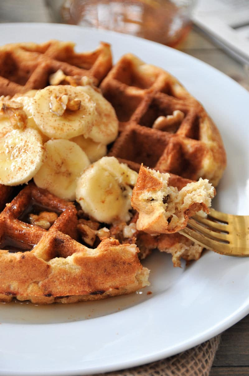 A banana bread waffle with banana slices, walnuts and cinnamon on top on a white plate. A gold fork is holding a piece of the waffle