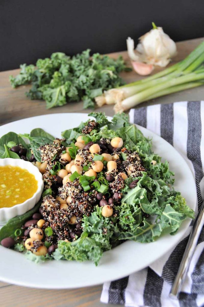 A protein packed superfood salad with black beans and chickpeas, kale and spinach. Healthy, delicious, and perfect for lunch or dinner.