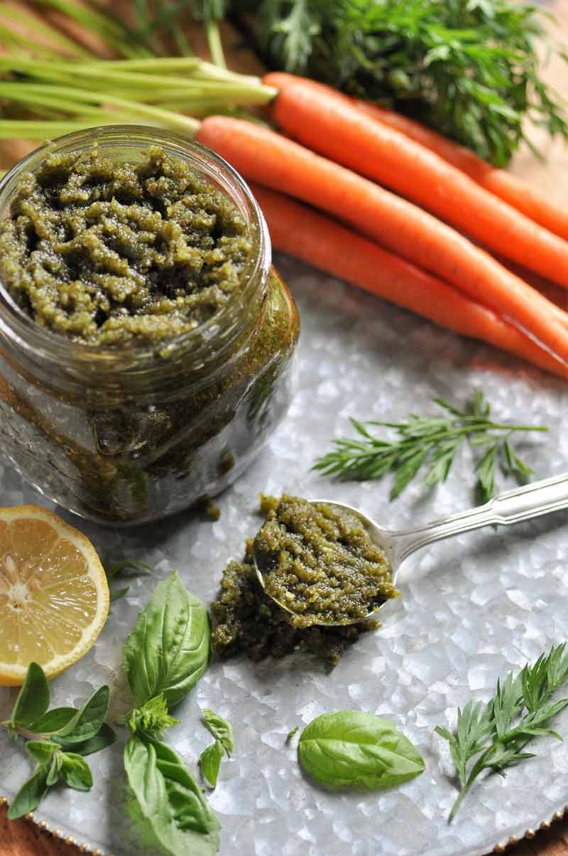 An overhead shot of a jar of pesto and a spoon of pesto with carrots, basil, greens, and lemon wedges.