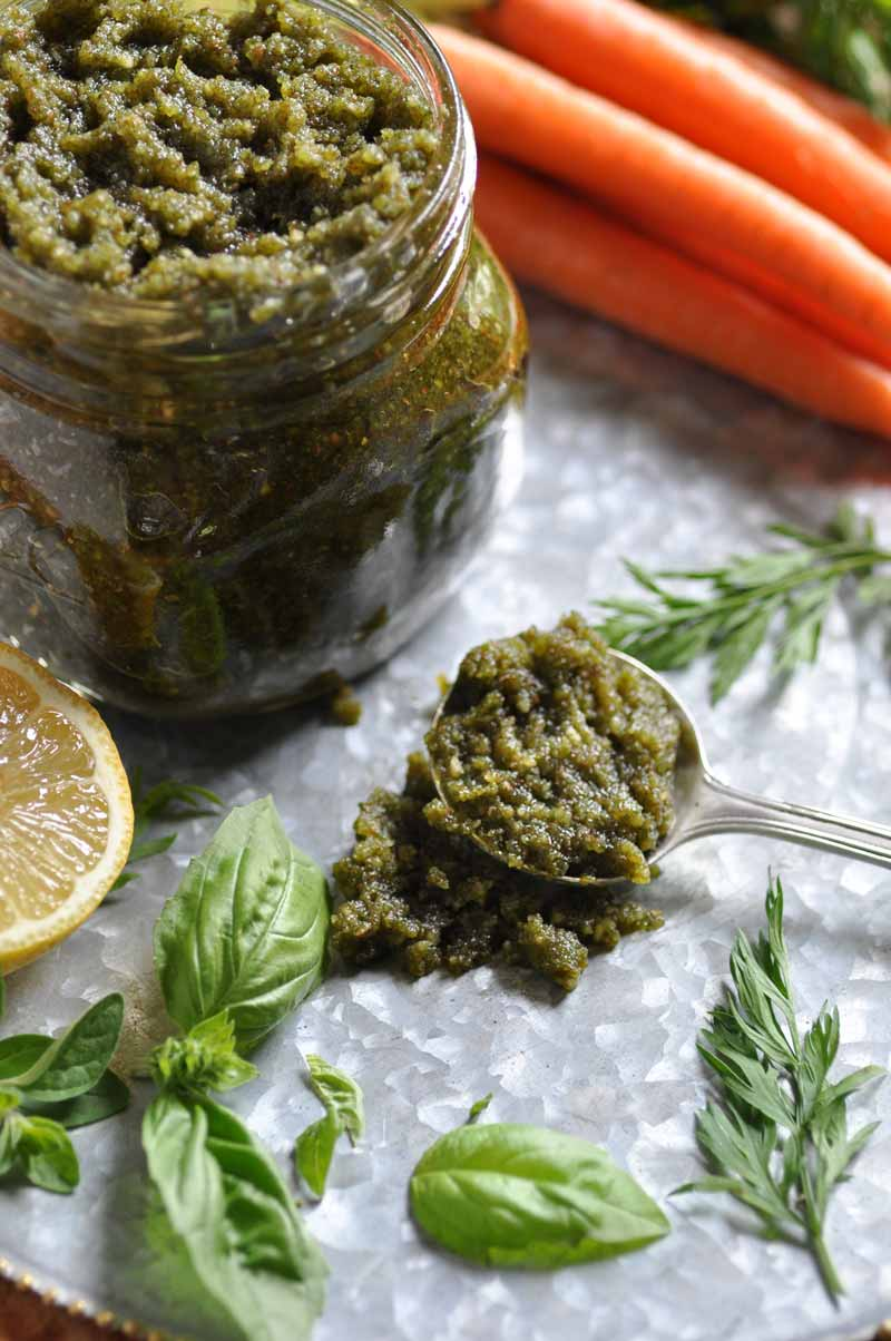 A glass jar of pesto with a silver spoon of the pesto and basil, carrots, greens, and lemons next to them.