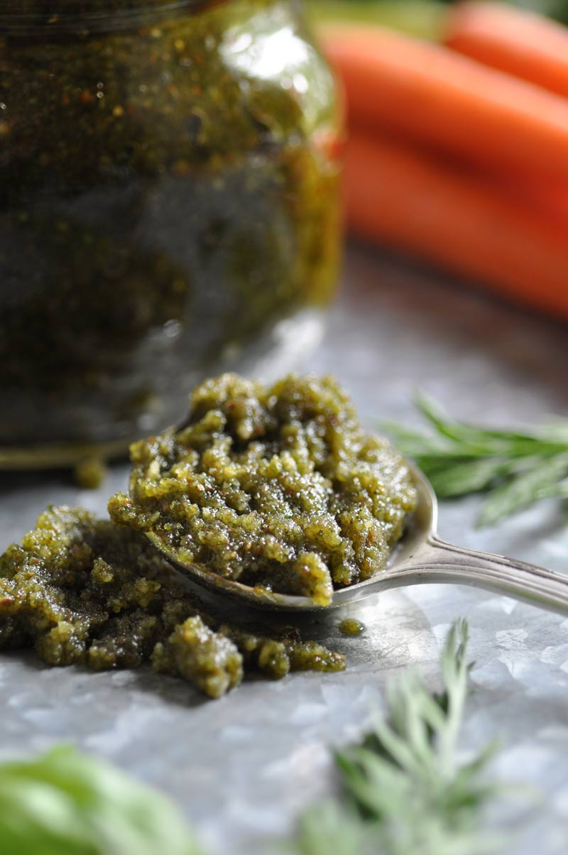 A close up of pesto on a silver spoon with greens and carrots and a jar of pesto in the background.